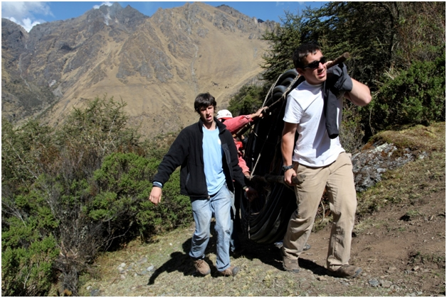 Ross, TJ, and 3 Peruvian villagers carrying 100 m of tubing up the hill to the site where 3 homes were serviced by the generator. This was an intense climbing exercise at 4000 m altitude. Ross and TJ had to rest frequently to ease their burning lungs.