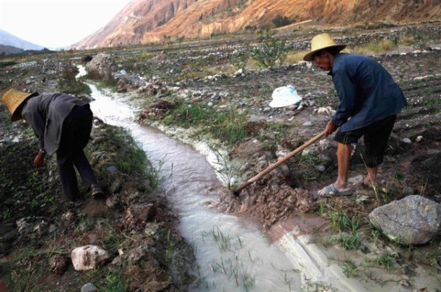 Farmers using the polluted stream in Yunnan Province, China to irrigate their farms.