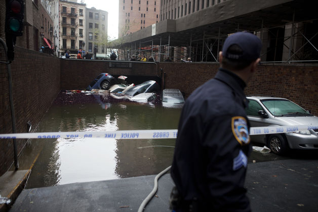 A police officer looks at vehicles submerged by flood waters that resulted from Hurricane Sandy in October of 2012. Source: Bloomberg.