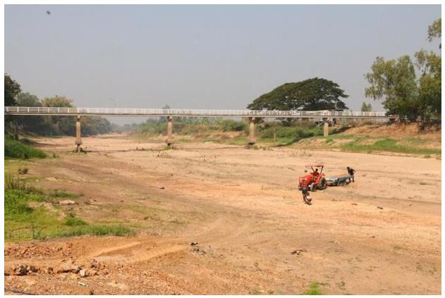 Figure 2. A tractor drives across the river bed of the Yom River, which dried out in January, in Phichit province in 2015.(Fernquest, 2015)