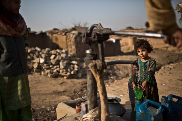 "Figure 1: Afghan refugees pumped water by hand in a slum of Islamabad, Pakistan. An official warned that Pakistan could become ""a water-starved country."""