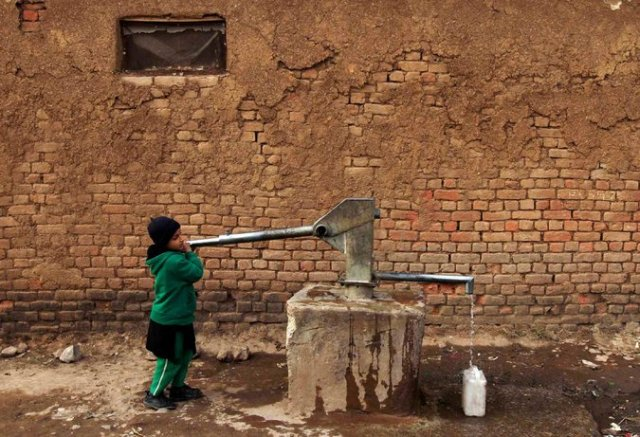 Figure 2: A girl collecting water for her family at a slum on the outskirts of Islamabad.